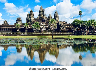 Angkor Wat seen across the lake with beautiful reflection of the monument and the cloudy sky into the water, Cambodia.