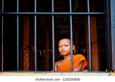 Angkor Wat, Siem Reap / Cambodia - OCT 22 2011 : young novice buddhist monk peeking looking outside of the window from his monastery