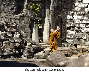 ANGKOR WAT - SIEM REAP - CAMBODIA. 03 NOVEMBER 2018. A Buddhist monk is taking pictures at the beautiful Angkor Wat in Siem Reap.  Angkor Wat is one of the largest religious monuments in the World.