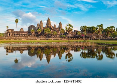 Angkor Wat sunny day blue sky main facade reflection on water pond sunset light. World famous temple in Cambodia, tourist travel destination.