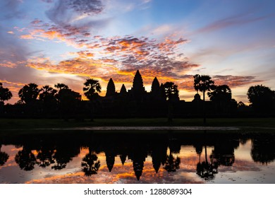 Angkor Wat Sunrise, The quintessential shot of Angkor Wat at sunrise is taken from behind the reflection pools, to see the vibrant red and the temple's stunning silhouette mirrored in the still water.