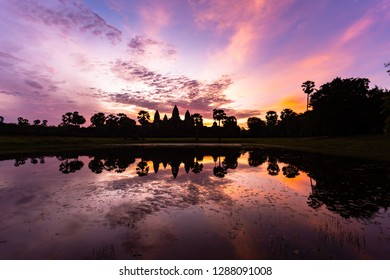 Angkor Wat Sunrise, The quintessential shot of Angkor Wat at sunrise is taken from behind the reflection pools, to see the vibrant red and the temple's stunning silhouette mirrored in the still waters