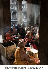 Angkor Wat/Cambodia - 05/18/2019: Picture of blessing ceremony with of Buddhist monk splashing holy water believer's heads on Visak Bochea day (Budda's birth), Angkor Wat, Cambodia