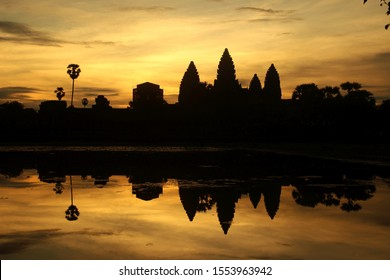 The Angkor Watt temple reflects on water in Camboia at sunrise hour