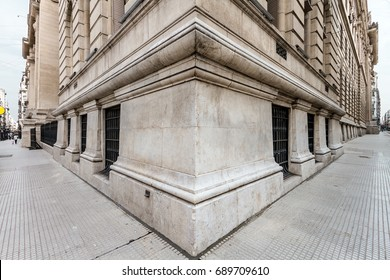 Angle of the corner of a neoclassical building with both sidewalks