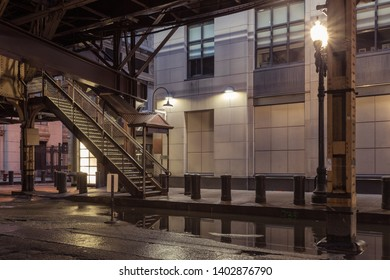 Angle of descending stairwell of an overhead train in downtown urban area with lights at night