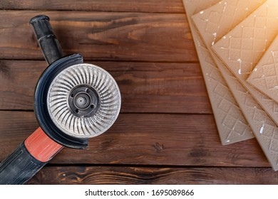 angle grinder and ceramic tile on a wooden background