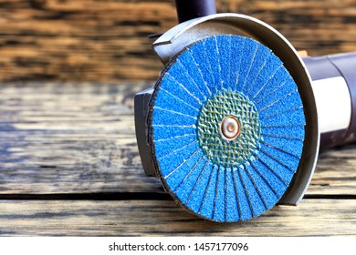 Angle grinder with grinding disc brushes and abrasive wire brushes lies on the background of a old wooden table.