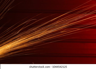 Angle grinder sparks, indoors shoot over red metal background