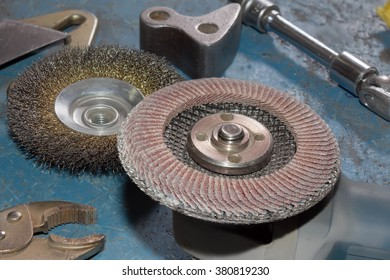 Angle grinder with wire brush for mechanical cleaning of metal and abrasive disk for grinder.