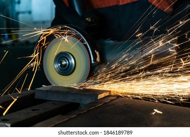 Angle grinder at work, sparks and dust from the cut-off stone