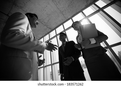 Angle view of business colleagues talking at the end of business meeting