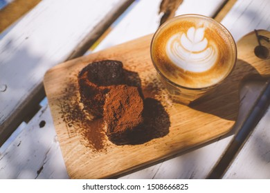 Angle view of chocolate butter bun with hot latte coffee on Chopping Wood.