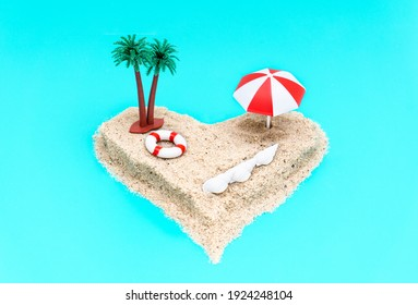 Angle view of a heart-shaped miniature toy island composition with palm trees, sun umbrella, a lifebuoy and seashells on a light blue background imitating the ocean. Romantic vacation concept.