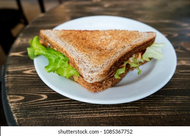 Angle view of triangle clubhouse sandwich on plate on wooden table