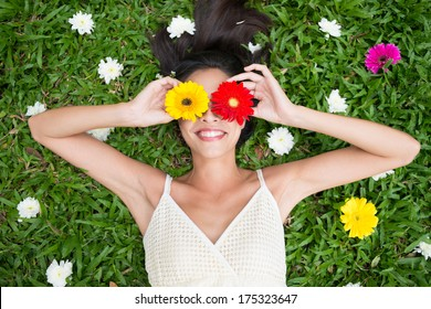 Angle view of a woman holding gerbera flowers on her eyes while lying on the grass