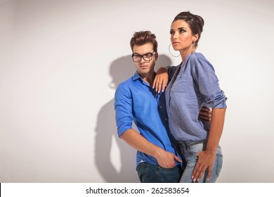 Angle view of a young fashion couple. The man is embracing the woman while looking down.