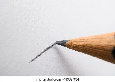 Angled close up (macro) of a graphite pencil drawing a line on textured white paper.