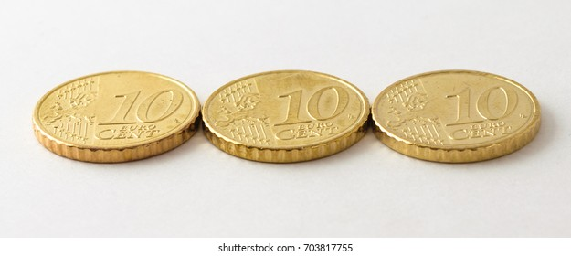 Angled close up of side of a horizontal line of three organized, clean and polished European ten / 10 cent coins on white high quality fibre paper