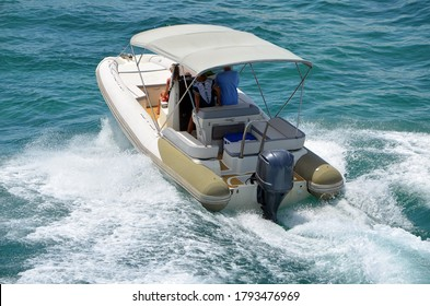Angled elevated view of a pontoon motor boat with a Bimini top.