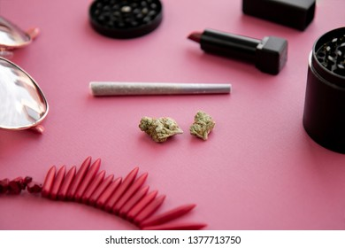 Angled Image of a Joint and Buds on Bright Pink Background with Lipstick, Necklace, Grinder and Heart Sunglasses