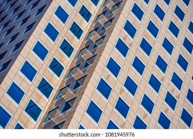 Angled lines and shaded facades of a modern architectural highrise.