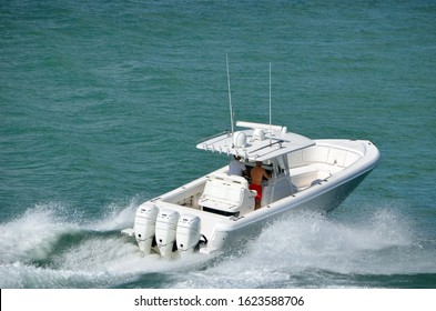 Angled overhead view of a white sport fishing boat powered by three outboard engines
