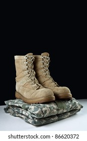 Angled photo of a pairr of tan leather Army combat boots placed together on camouflage uniform on black background