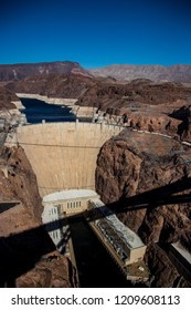 Angled picture of hoover dam during morning sun with shadow of bridge striking across the surface rocks