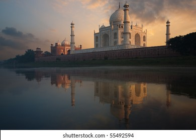 The angled riverside Taj Mahal rear glows brilliantly from a colorful orange sunset seen on the waterfront reflected in the holy Jamuna river in Agra, India. Horizontal copy space