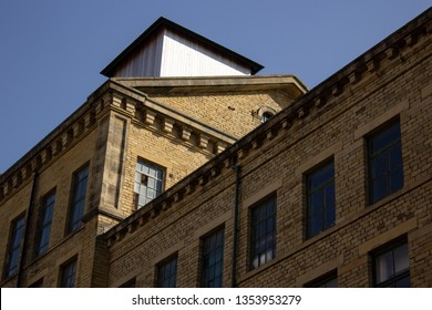 An angled roofline against a blue sky provides light and shade, gold and blue