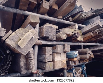 Angled shot of various fence posts and wooden beams at a salvage yard in the UK.