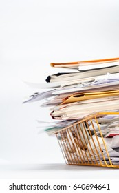 Angled shot of a yellow wire office filing or in tray, stacked high with a messy pile of documents. Copy space on white background to left and above.