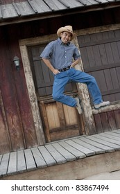 Angled vertical image of an Asian man in country garb kicking his heels in the air, as he jumps / dances in front of a western backdrop.