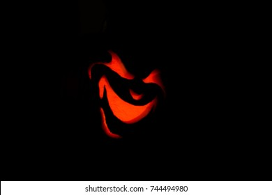 Angled view of angry jack-o-lantern face lit up by candle and pumpkin blacked out and glowing red evil smile