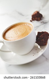 Angled view of cappuccino or latte coffee with chocolate brownie cookie on marble table