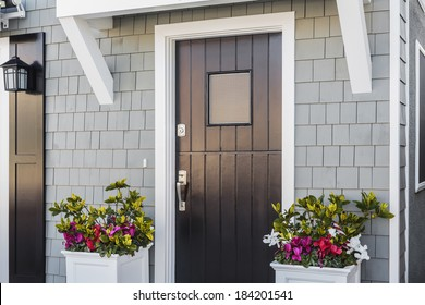 Angled view of glossy black front door to a family home; The door is made of vertical wood boards, with a window. It is framed by two flower planters, gray shingles of the house, and a door mat.