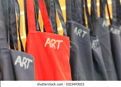 angled view of new red and blue art aprons smocks hanging neatly organised in the art room at a school. see many alternate views on my page.