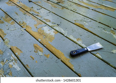 Angled view of a putty knife laying on gray wooden boards next to paint chips.
