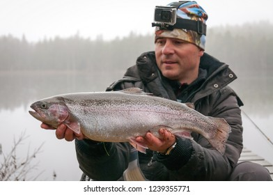 Angler with autumn fly fishing trophy - rainbow trout