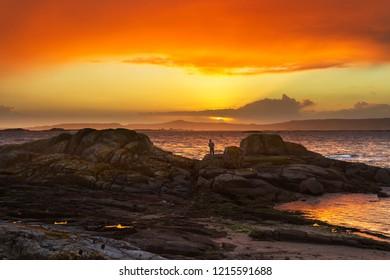 Angler between coastal rocks at red sunset in Arousa Island, Galicia, Spain