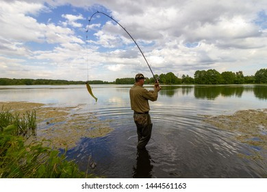 angler catching the fish in the lake during summer day