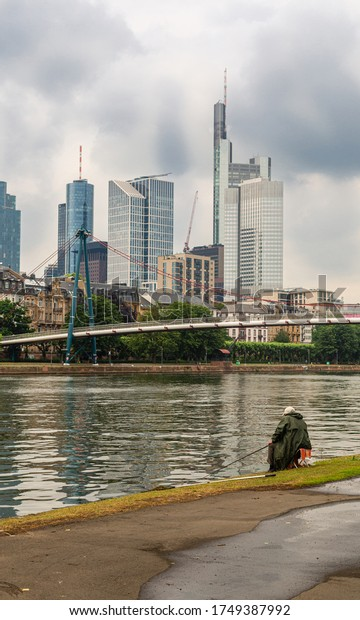 Angler catching fish in the river. View of the skyscrapers in Frankfurt am Main. City development. Relax and rest on the river. Cloudy sky.