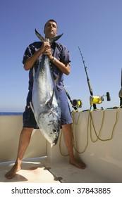 Angler fishing big game bluefin tuna on Mediterranean saltwater
