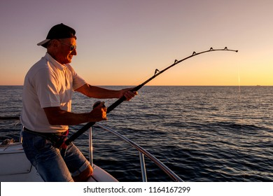 angler fishing on the sea from the boat at sunset