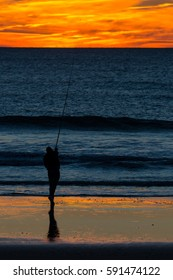 Angler with fishing rod on the beach