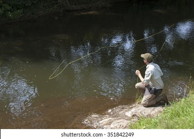 ANGLER FLY FISHING ON AN ENGLISH RIVER UK - JULY 2013 - Man fly fishing on River Lyd Devon UK
