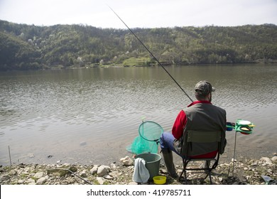 Angler With His Back Towards Camera Sitting On The River Coast Enjoying Angling And Beautiful Nature