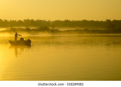 Angler on a boat catching a misty morning on the river