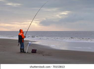 Angler on an deserted beach at sunset